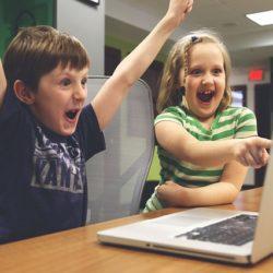 Dzieci cieszące się przed ekranem laptopa