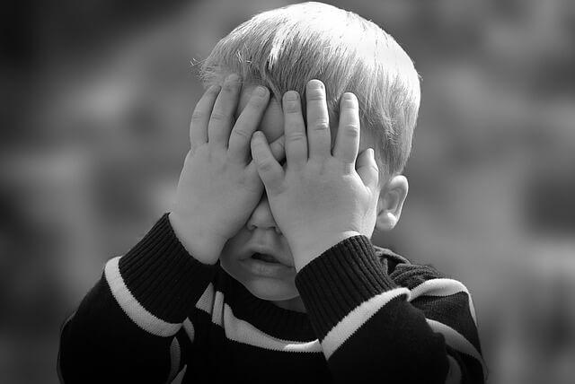 Chłopiec zakrywający oczy dłońmi