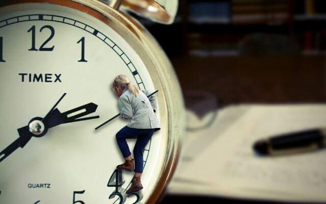 Stoper. Kobieta wspinająca się po zegarze.