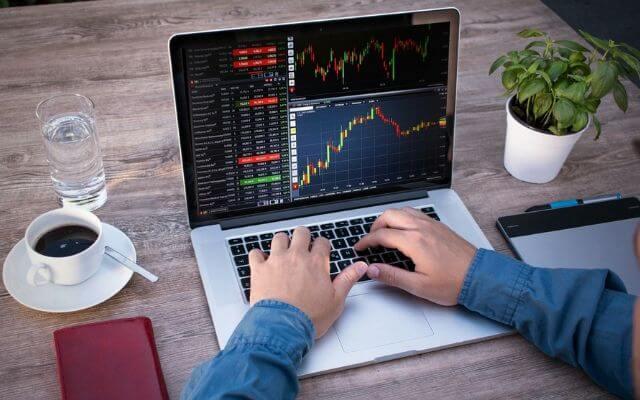 Ekran laptopa z notowaniami giełdowymi w postaci wykresu świecowego