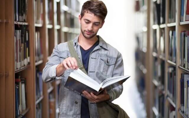 Mężczyzna czytający książkę w bibliotece. Nauka Excela.